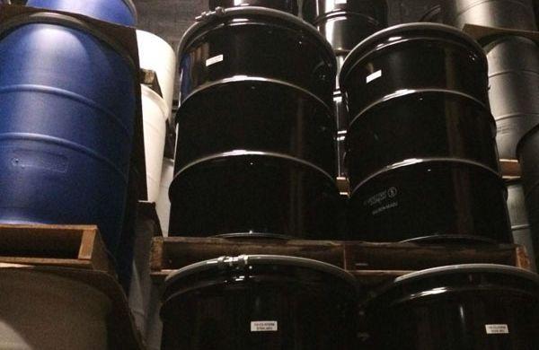 Open head black steel drums.